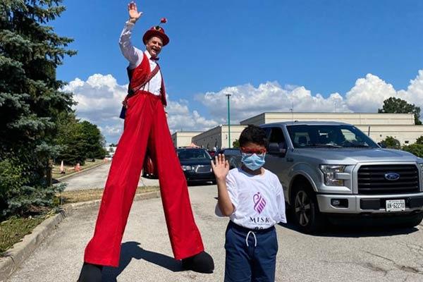 Eid Toy Drive - boy and man on stilts