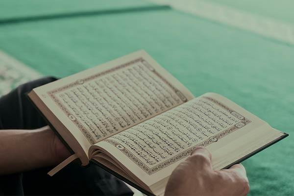 Hands holding an open book, the Quran